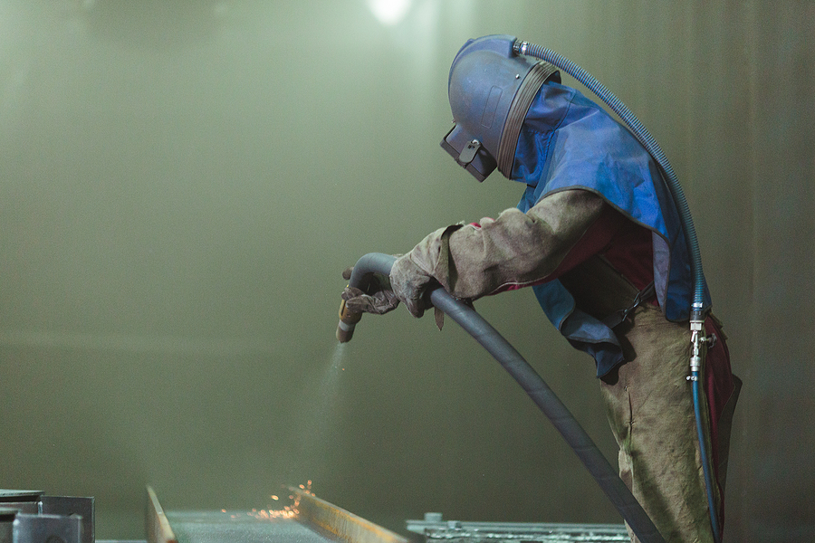 Worker doing a mobile sand blasting