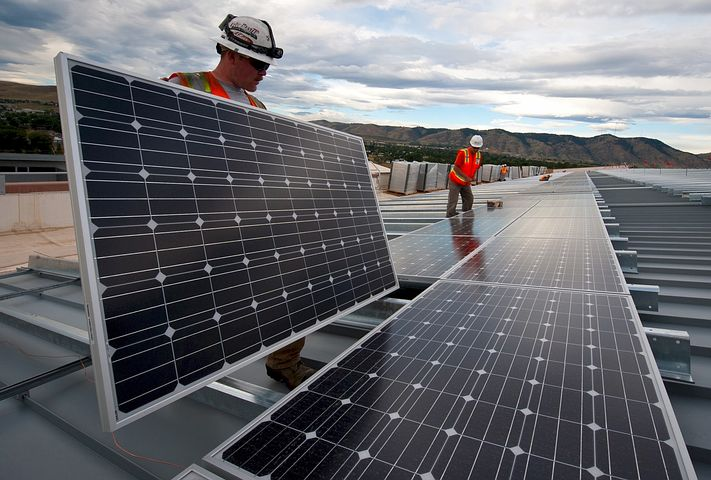 Two workers installing commercial solar